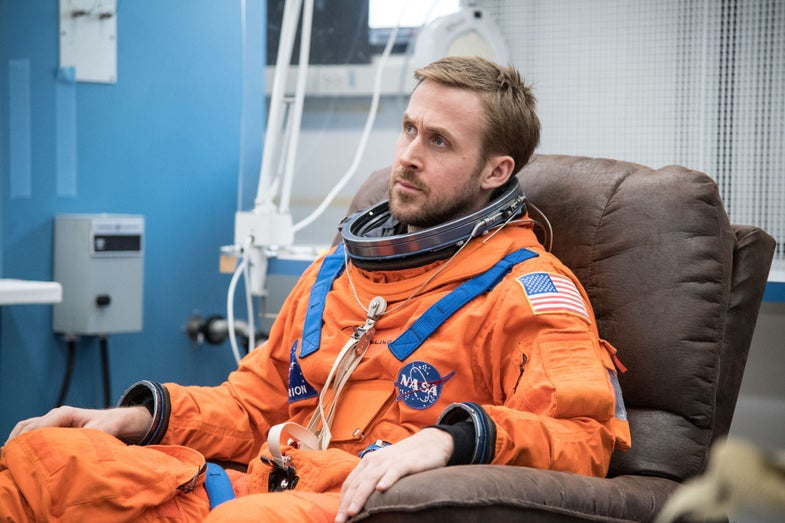 ryan gosling sitting in orange NASA uniform