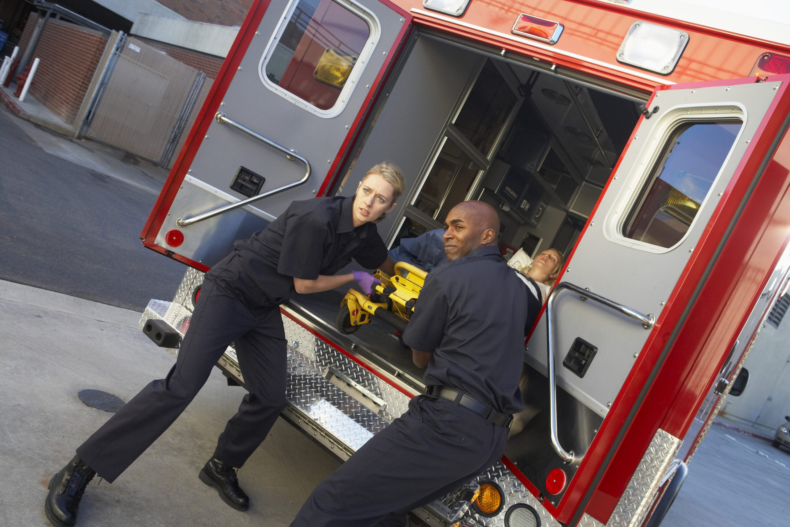 two paramedics prepare to take someone out of an ambulance