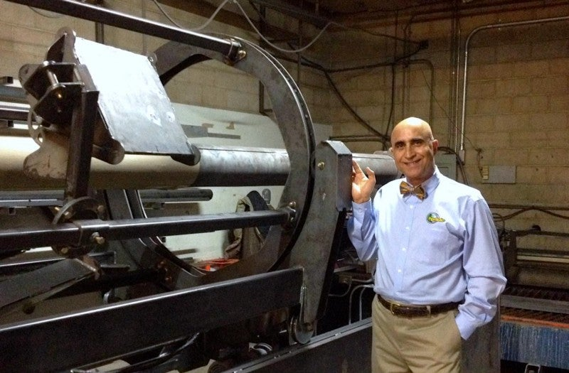 Ehsani stands next to a prototype of the machine that allows people to manufacture pipes on a truck or boat.