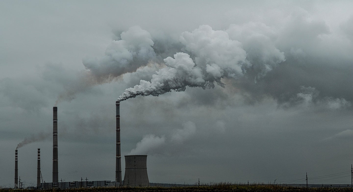 Smoke billows out of tall cement smokestacks against a grey sky.
