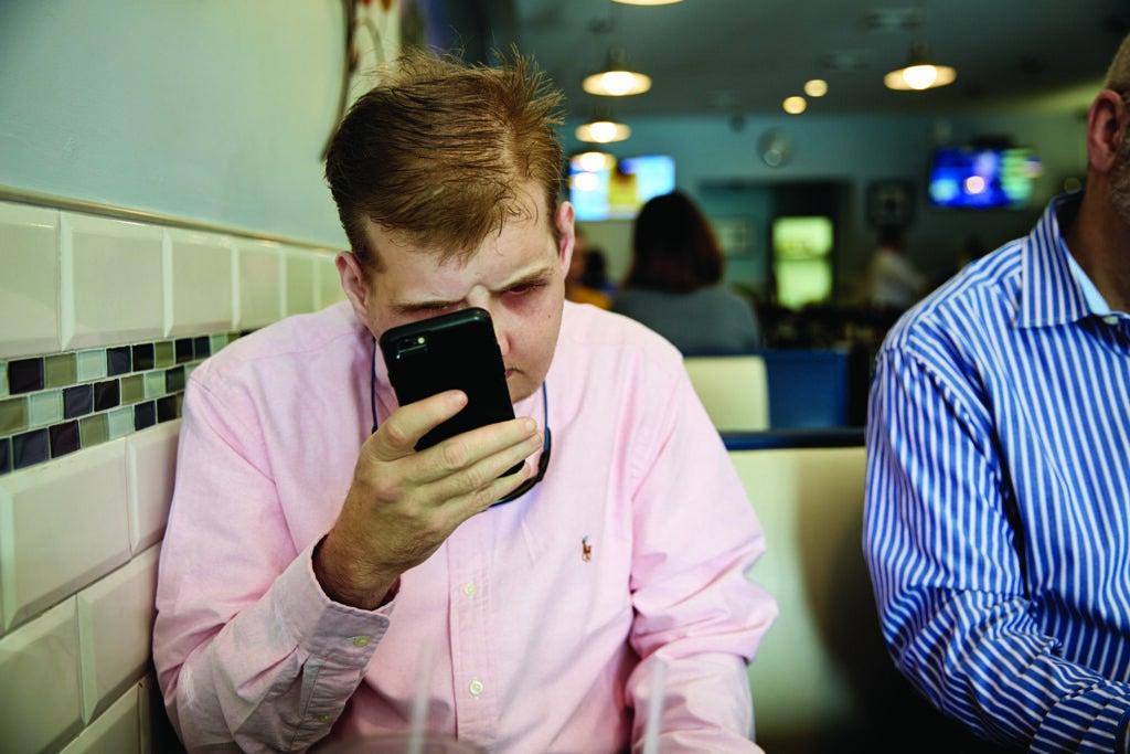 Patrick Hardison checks his cell phone.
