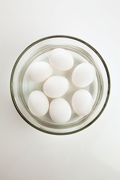 Seven eggs in a glass bowl of water.