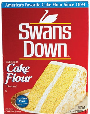 A photo of a box of cake flour with a yellow cake with vanilla frosting on the front.