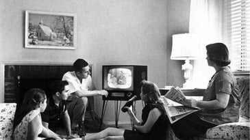 black-and-white photo showing a family watching TV in 1958