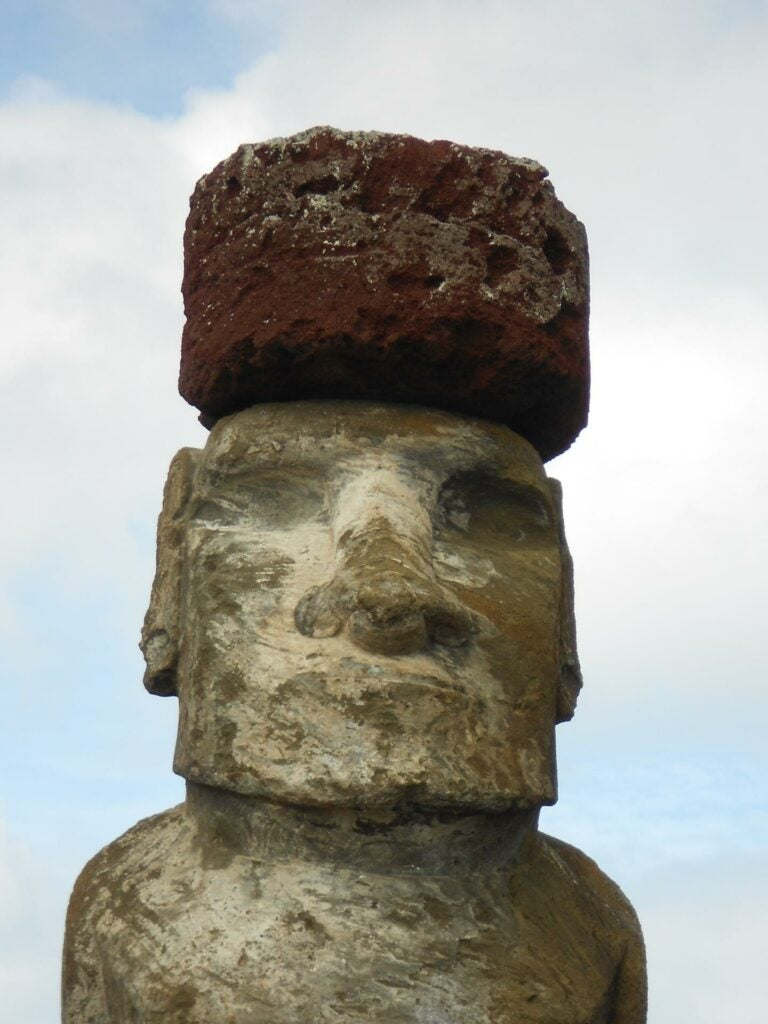 an easter island statue with a large rock hat