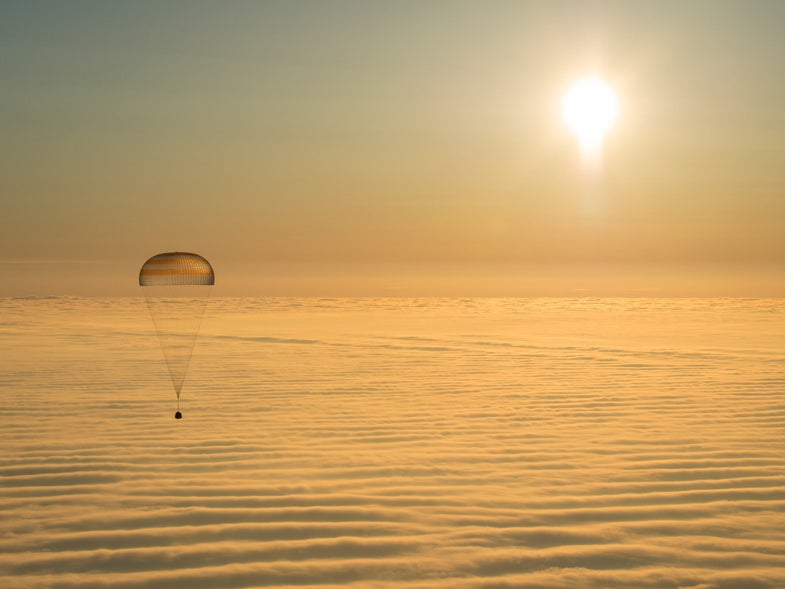 astronaut above the layer of clouds that line the bottom of this image.