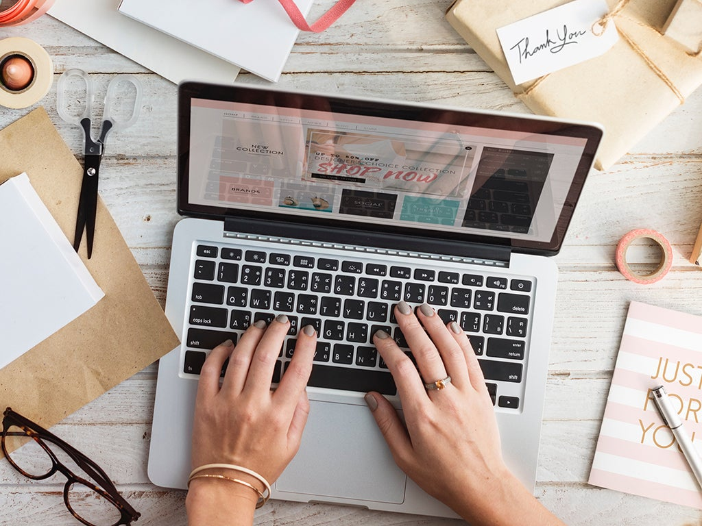 a person using an Apple laptop on a wooden desk with various materials around