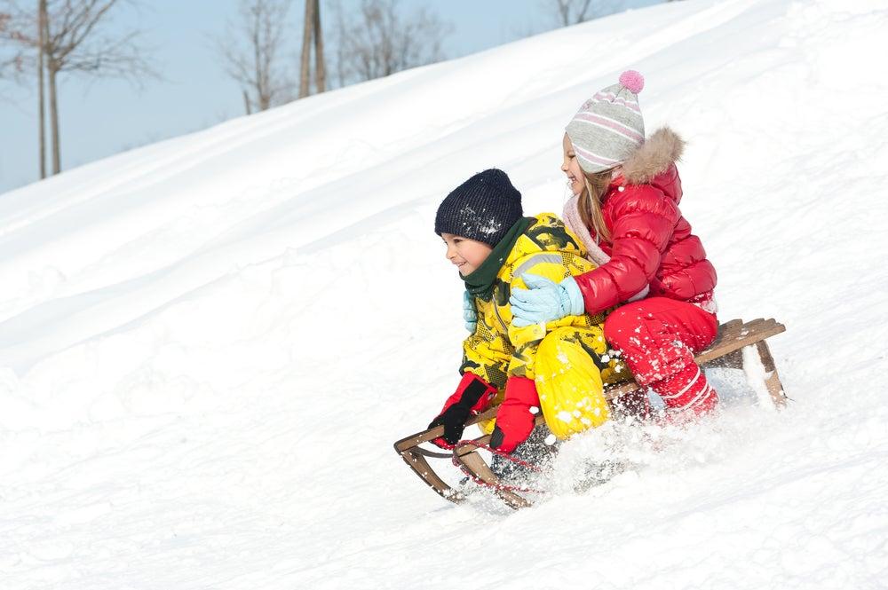 two children sledding downhill