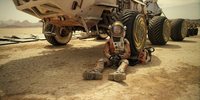 Matt Damon leans against a rover