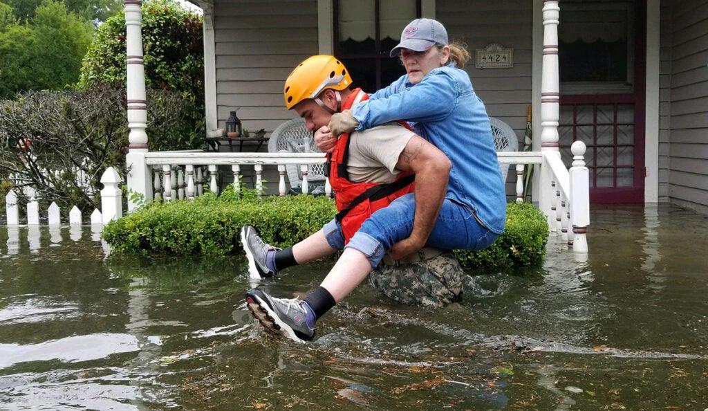a man carries a woman through a flood