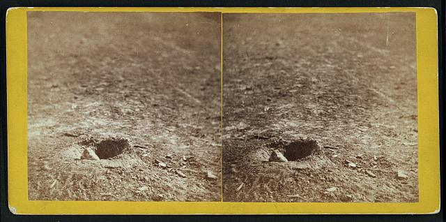 two holes in the ground with prairie dogs peeking out