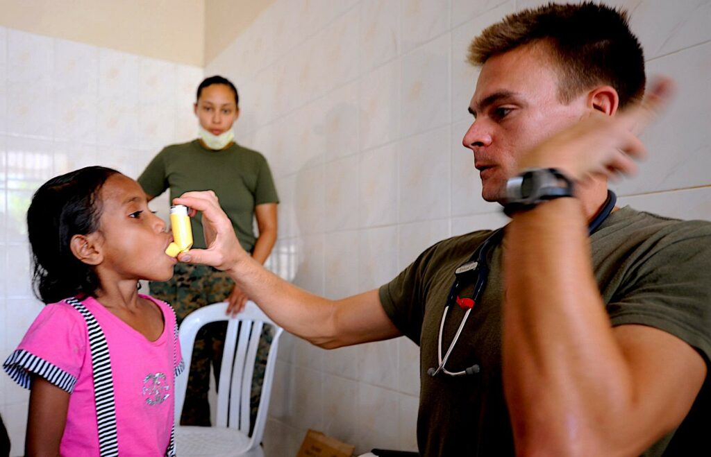 an adult shows a child how to use an inhaler