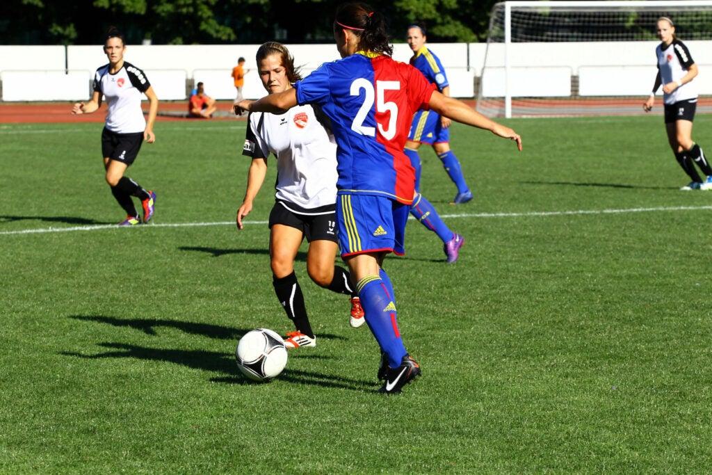 women playing soccer on turf field
