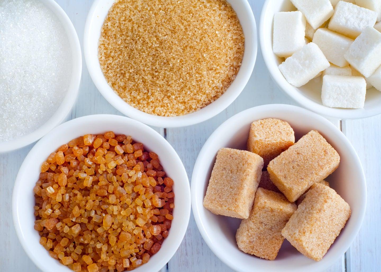 White bowls of white sugar, brown sugar, cane sugar, and unrefined sugar
