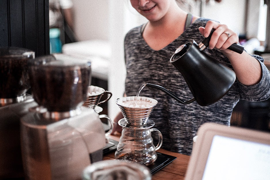 Woman pouring water from an electric kettle into a pour over coffee maker