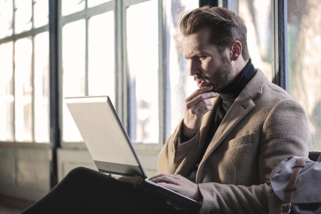 man thinking while using laptop