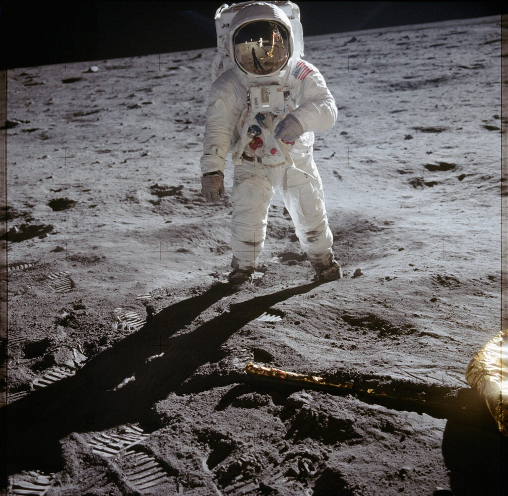 Astronaut Buzz Aldrin walks on lunar surface near leg of Lunar Module