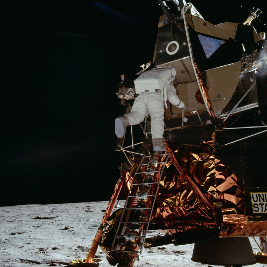 Astronaut Buzz Aldrin descends steps of Lunar Module ladder to walk on moon