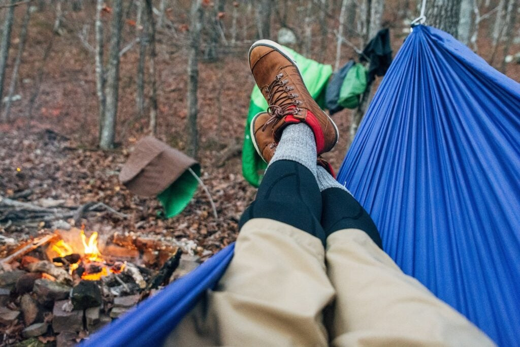 person camping in hammock near a campfire in the woods