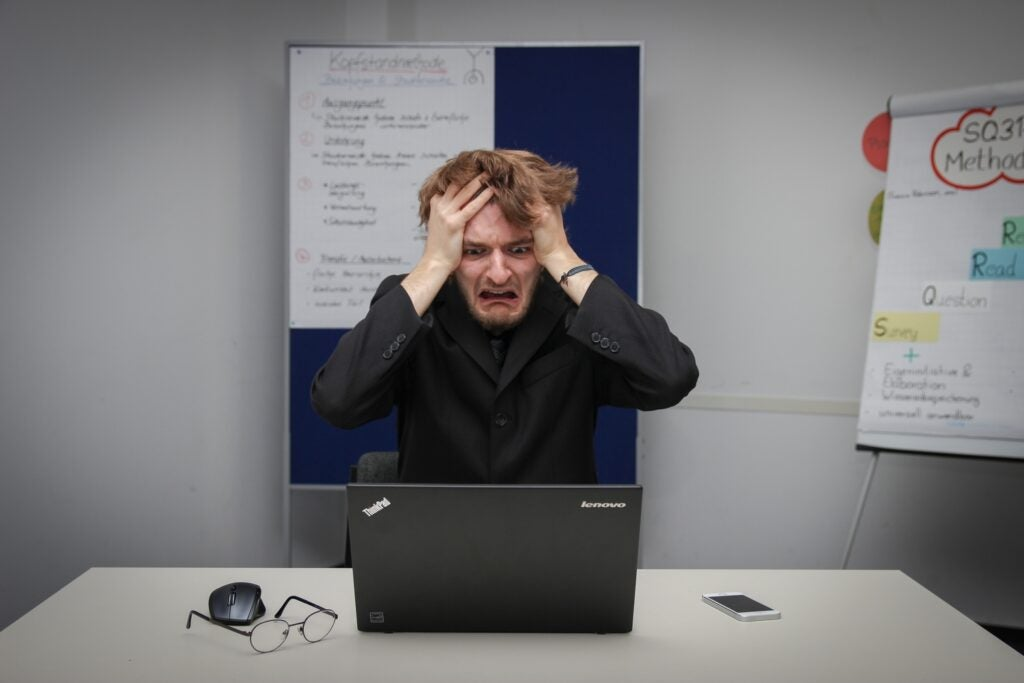 Man pulling his hair in front of a laptop