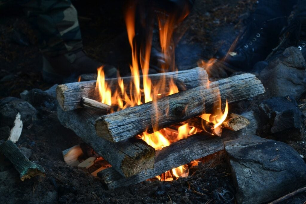 firewood stacked over a fire`