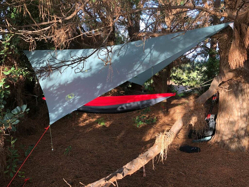 a tarp covering a hammock in the woods