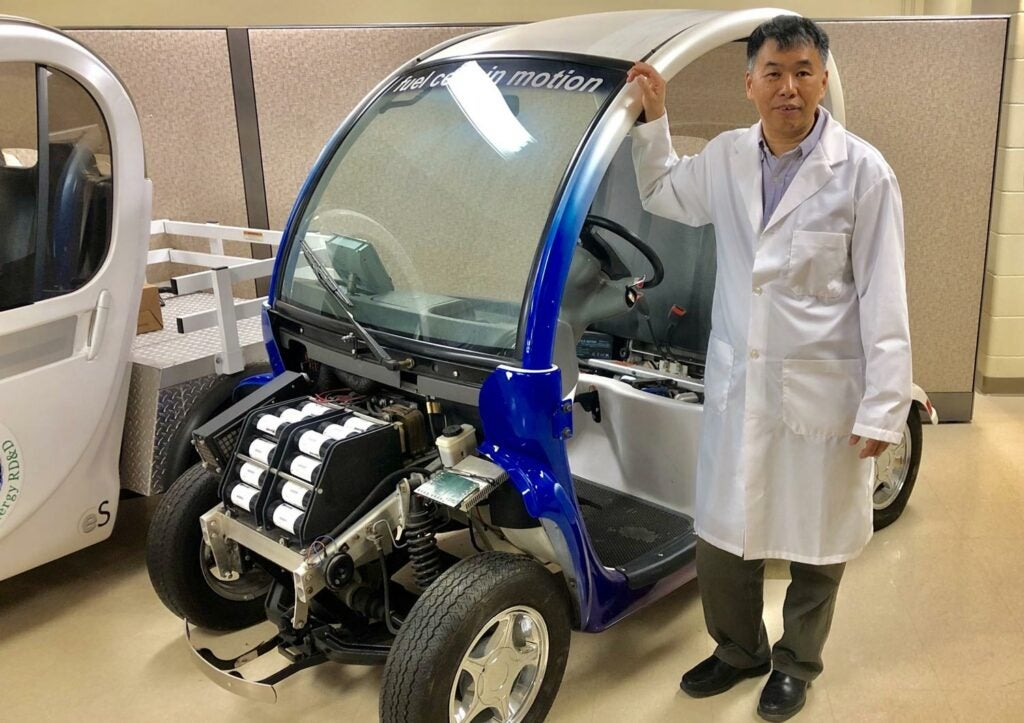 Professor Xianguo Li with his fuel cell test vehicle in his lab