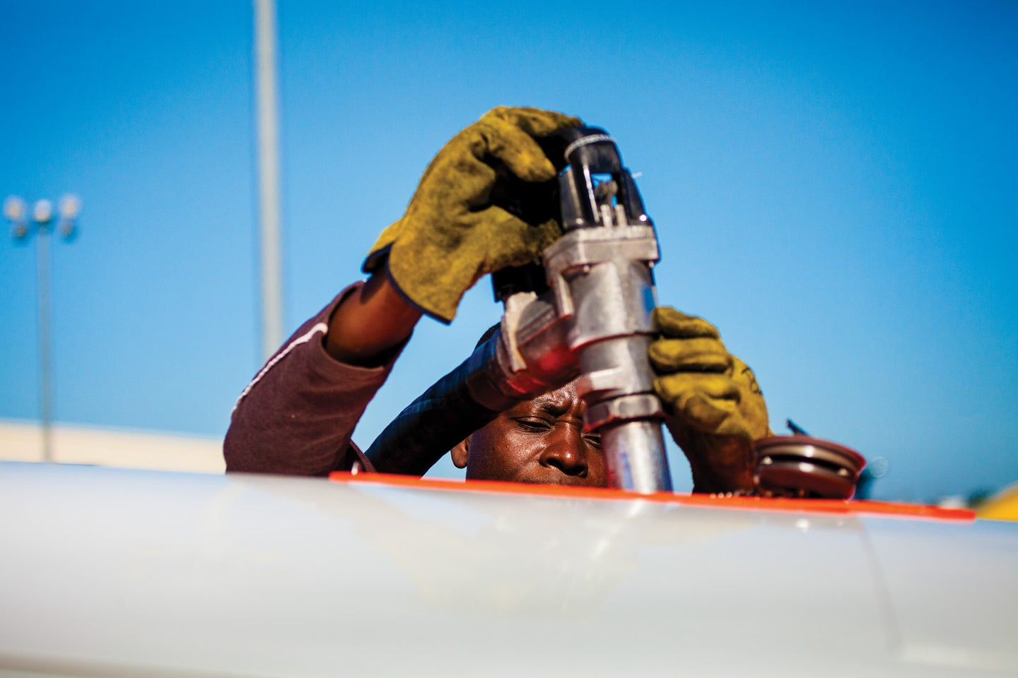 man pumping fuel into airplane
