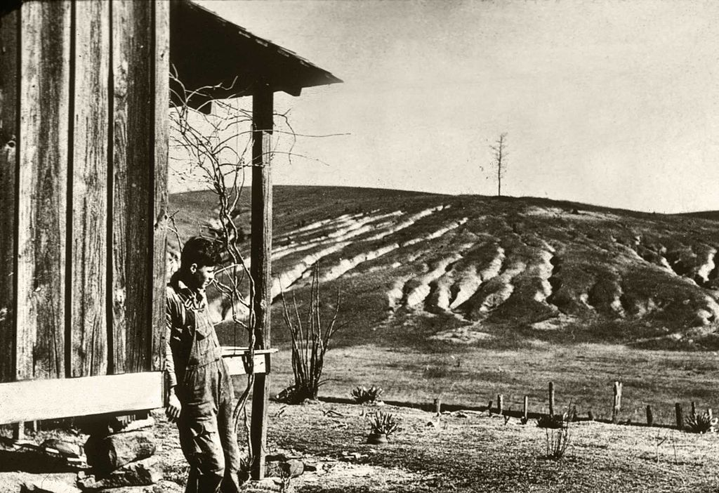 A man looks at an extremely dry and eroded farm