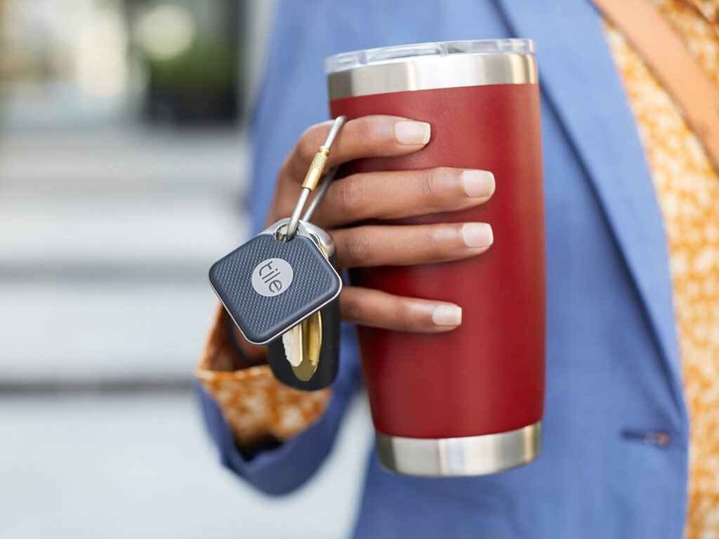 Person grabbing coffee mug and key chain with tile tracker