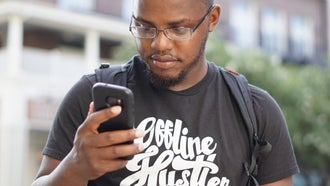 A Black man wearing a t-shirt, a backpack, and glasses, looking annoyed at a spam call on his cell phone.