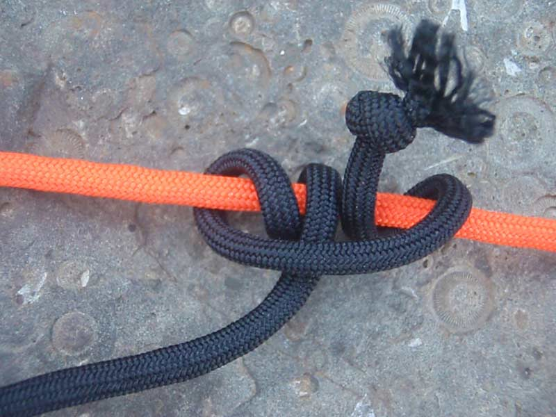 a rolling hitch knot with orange and black paracord