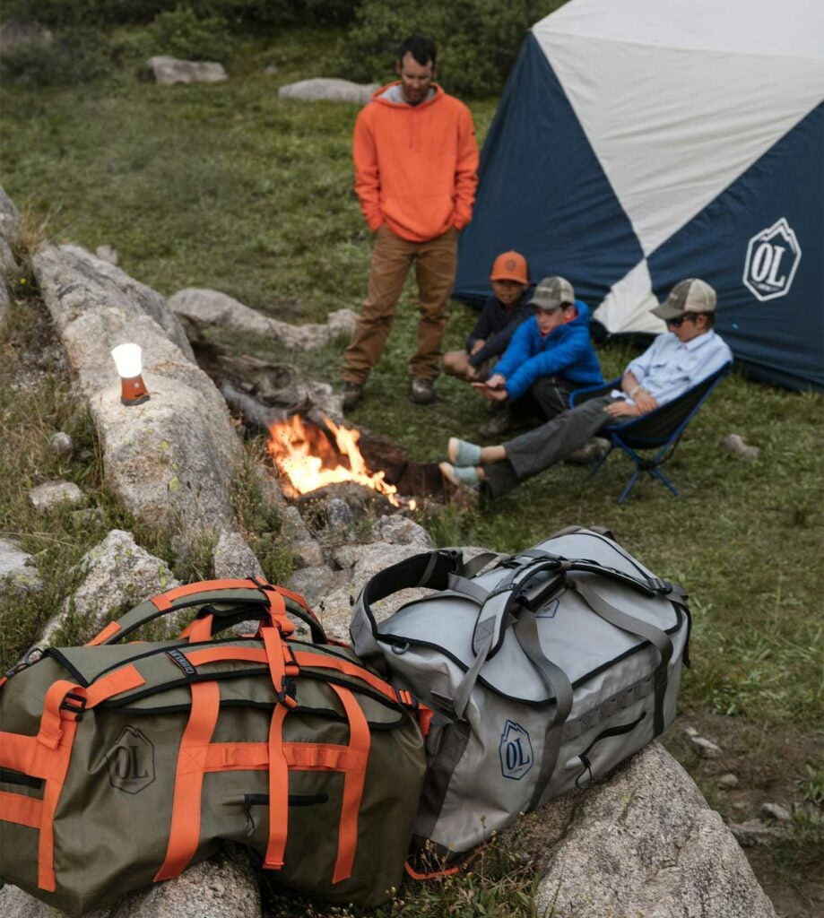 camping gear bags on a rock near men at campfire