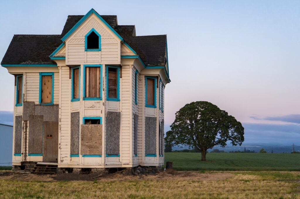 a boarded up house on open land