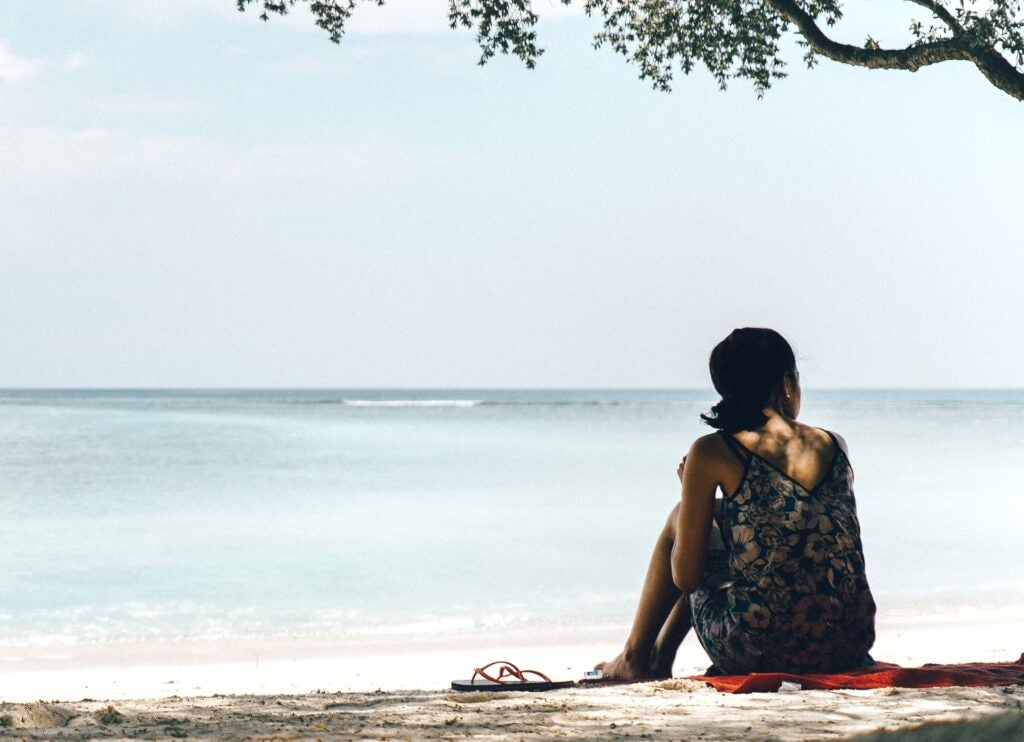 Woman sat on the beach under the shade of a tree