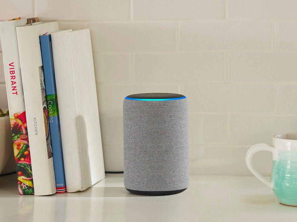 the amazon echo plus on a white table next to books and a mug