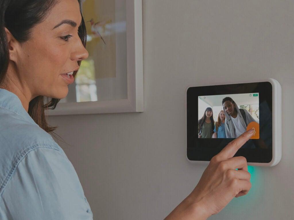 Woman touching the screen of a vivint hub