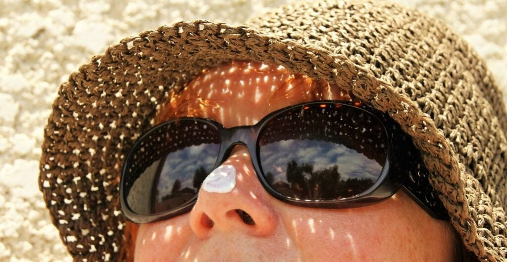 person wearing sunglasses hat and sunscreen on nose