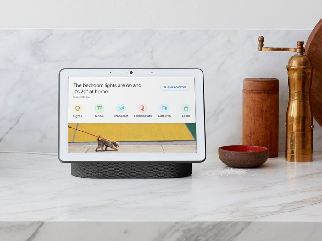 The google nest hub max on a white marble countertop next to a copper pepper mill