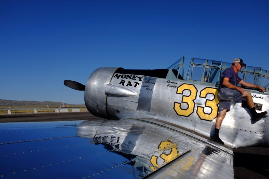 man standing on vintage airplane wing