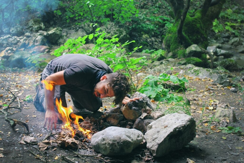 man lighting a fire in the outdoors