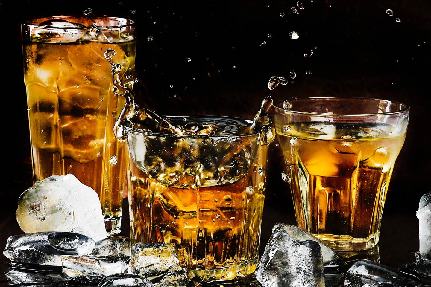 alcohol and ice in multiple glasses