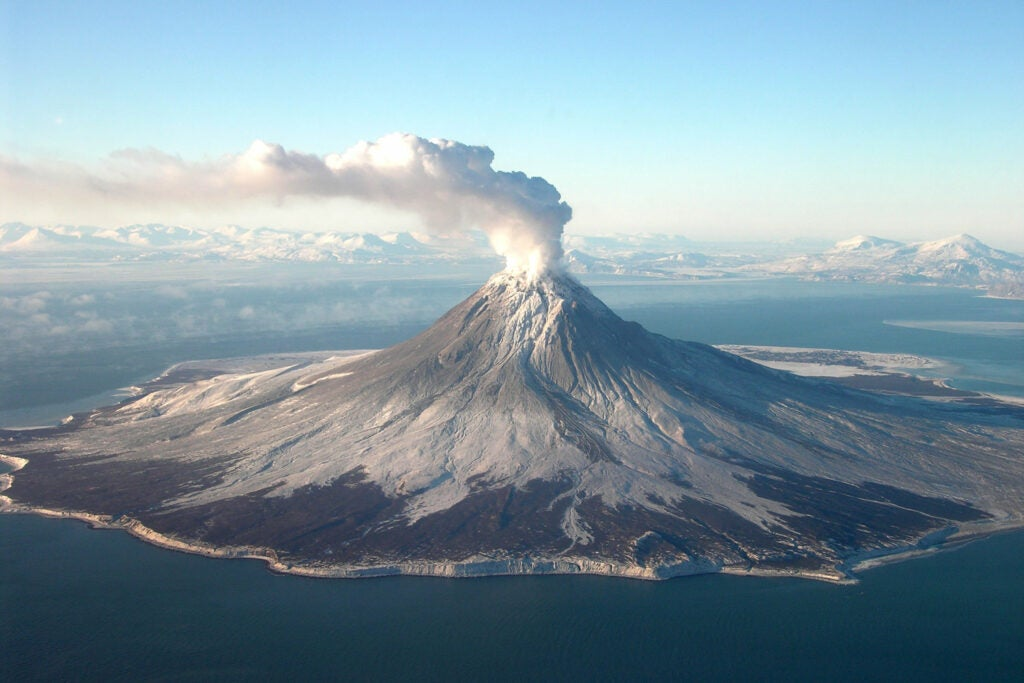 volcanic mountain with smoke coming out the top