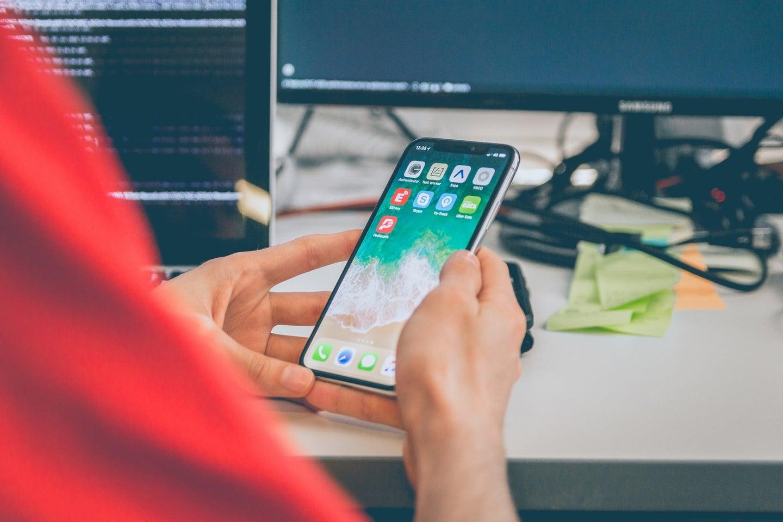person looking at phone screen at desk