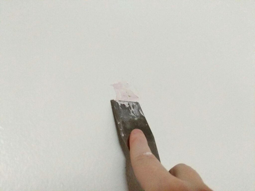 a person smearing putty over a hole in drywall with a putty knife