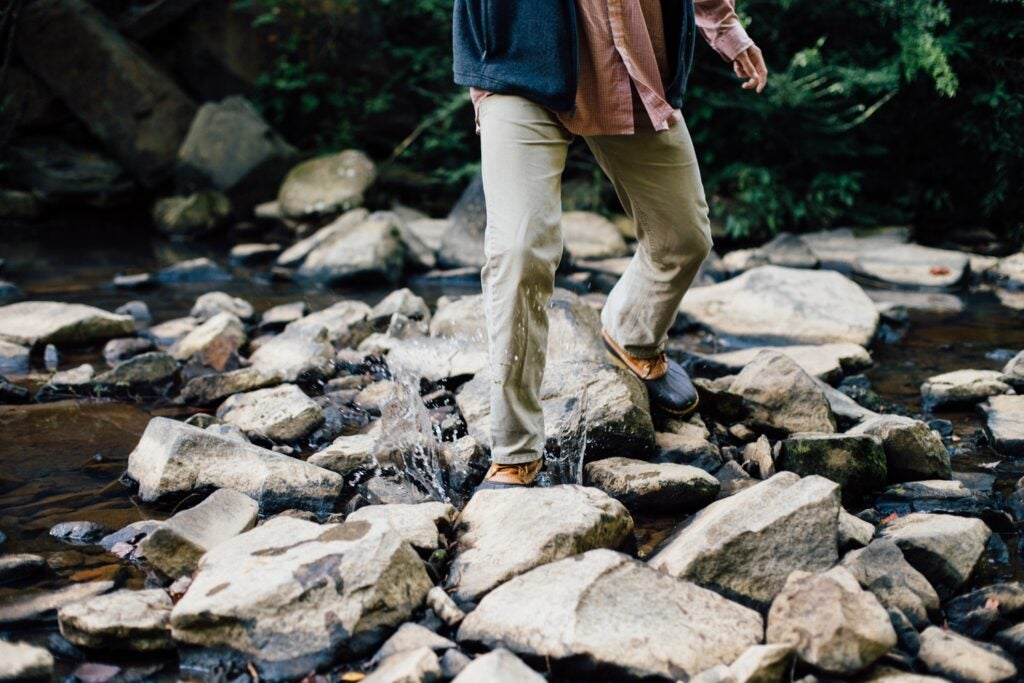 a person crossing a rocky stream while wearing long pants and boots