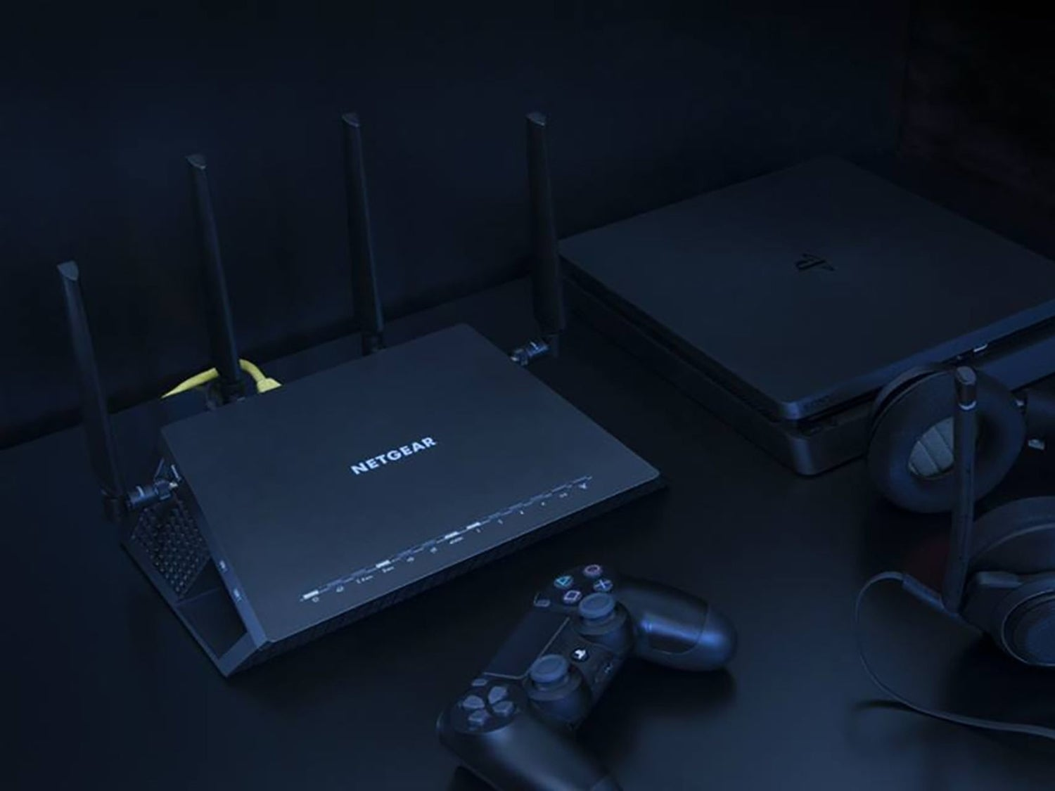 A Netgear router near a PlayStation video game console and headphones.