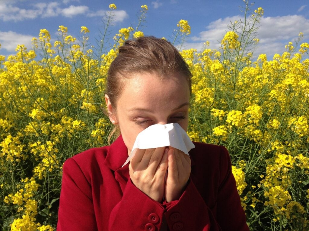 a woman blowing her nose into a tissue in front of a field of flowers