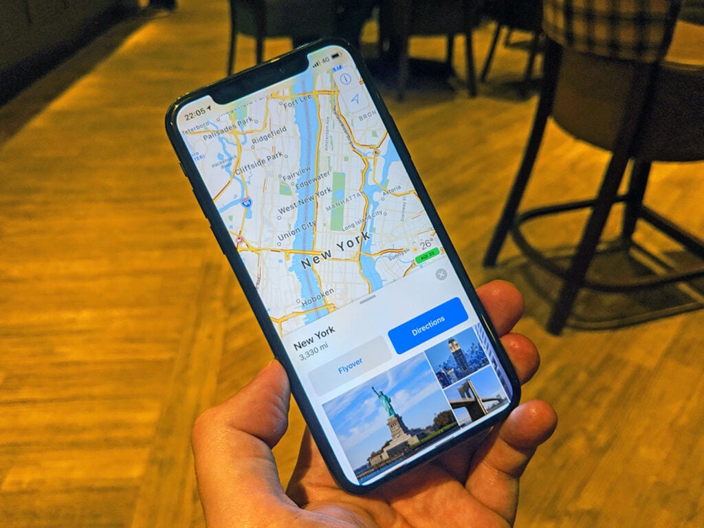 hand holding an iphone showing apple maps on the screen