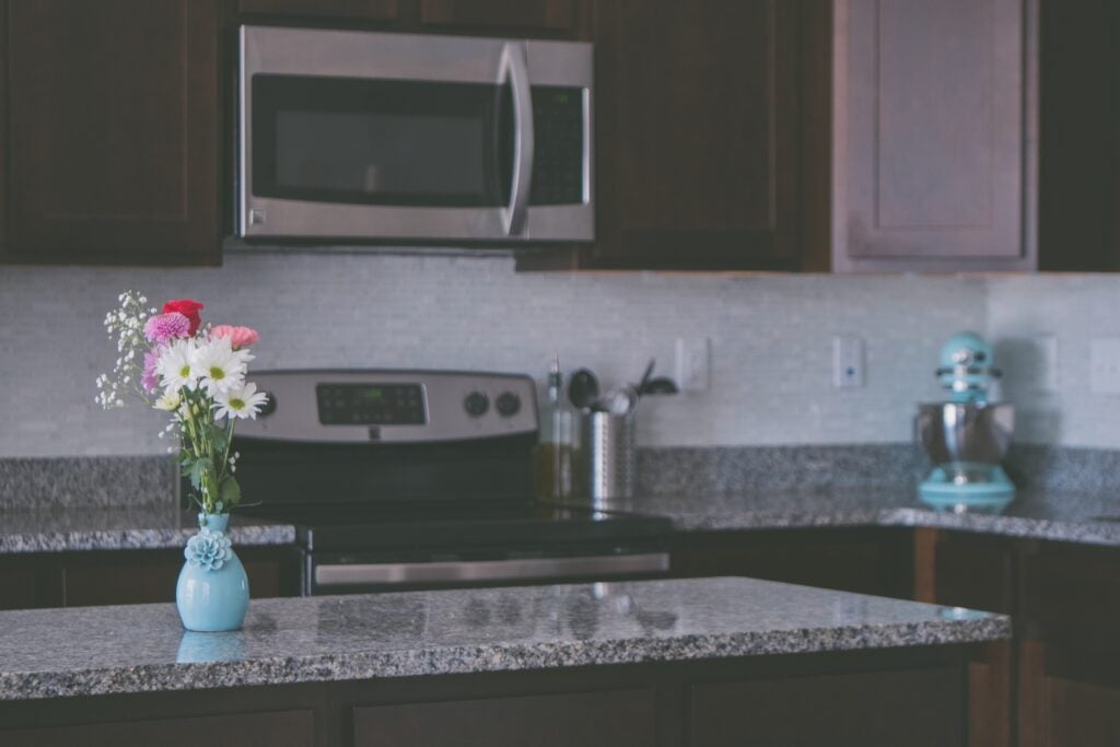 a vase of flowers on a kitchen counter near a microwave